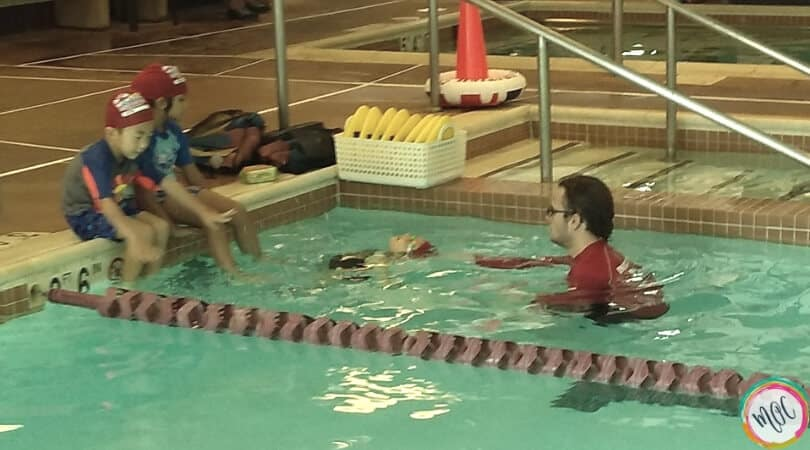British swim school turtle level 1, girl in red swim cap doing back stroke to her instructor.