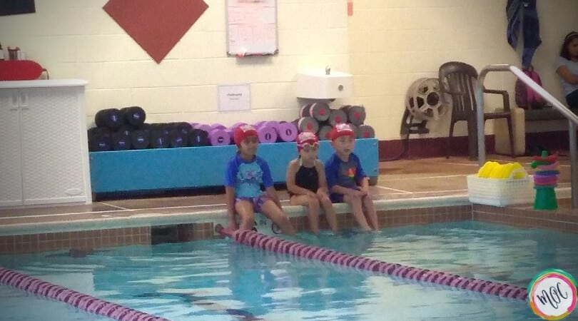 3 children in their red turtle 1 british swim school caps sitting on the side of the pool waiting for their turn at the lesson..