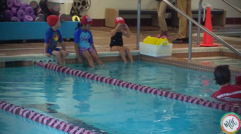3 children sitting at the side of the pool in their red turtle 1 british swim school caps, waiting their turn for the lesson. One child getting her goggles on.