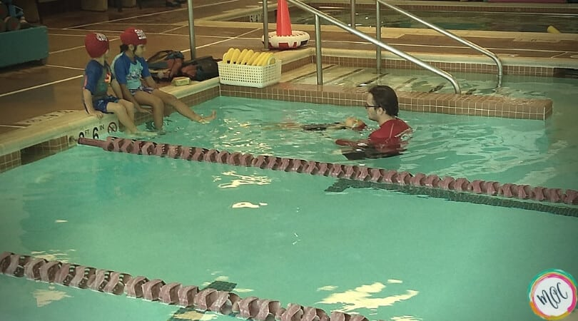 Child doing backstroke for turtle 1 british swim school lesson with instructor.
