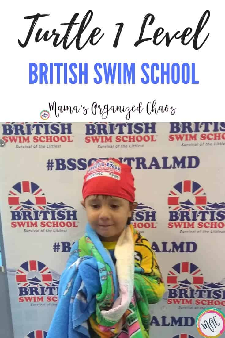 Graduation picture from minnow level to turtle 1 level in british swim school. Girl has her new red swim cap on standing in front of BSSCENTRALMD sign.