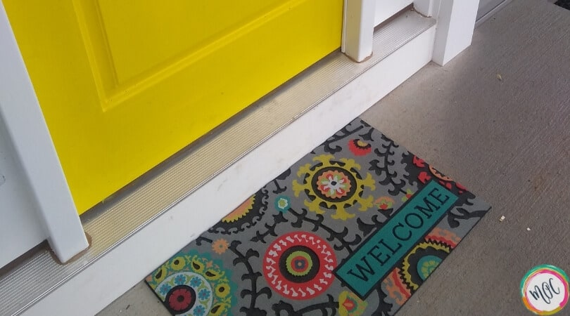 yellow door with colorful welcome mat