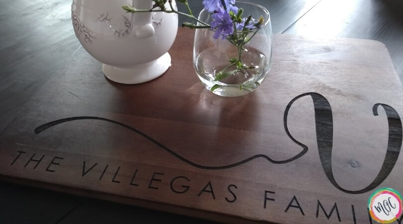 "cutting board with ""the villegas family"" written, and purple flowers with a white vase"