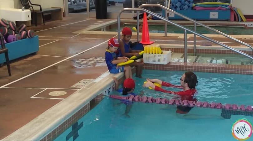 turtle 1 level red swim caps for british swim school, children sitting at edge of the pool during class.