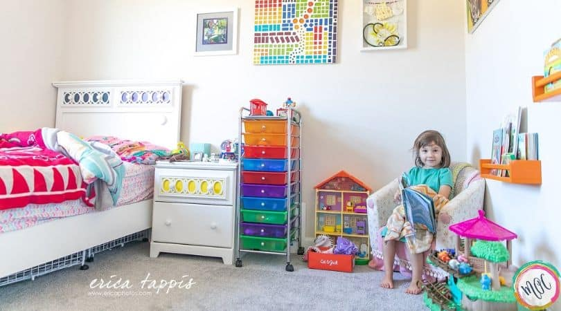 4 year old girl sitting in her colorful room reading a book